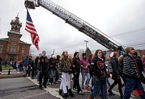Chardon High School students walk under a large American flag on the town square in Chardon, Ohio Wednesday, Feb. 27, 2013 during a memorial march for 3 students killed in a shooting at the school last year. Photo / AP - Mark Duncan
