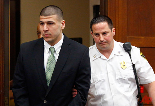 In this May 28, 2104, file photo, former New England Patriots footballplayer Aaron Hernandez is led into the courtroom to be arraigned on homicide charges at Suffolk Superior Court in Boston. Hernandez's lawyers want a judge to transfer the him to a jail closer to Boston, citing safety and other concerns. In a request filed Friday, June 20, 2014, his Boston-based attorneys say they have to travel too far to meet him at the Bristol County jail. (AP Photo/Dominick Reuter, Pool, File