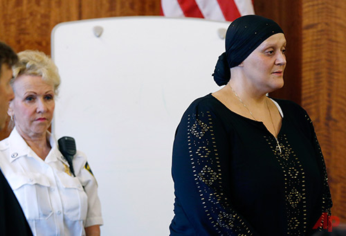Tanya Singleton, right, stands on the witness stand to plead guilty as her lawyer E. Peter Parker, far left, looks on during a hearing in Fall River Superior Court in Fall River, Mass., Tuesday, Aug. 12, 2014. Singleton, a cousin of former New England Patriots football player Aaron Hernandez, pled guilty to criminal contempt in connection with the investigation of murder charges against Hernandez. (AP Photo/Michael Dwyer, Pool)