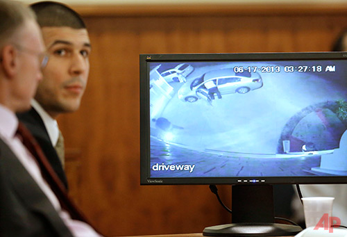 Former New England Patriots football player Aaron Hernandez and defense attorney Charles Rankin, left, look on as video from Hernandez's home is displayed on a monitor during his murder trial, Thursday, Jan. 29, 2015, in Fall River, Mass. Hernandez is charged with killing semiprofessional football player Odin Lloyd, 27, in June 2013. (AP Photo/Steven Senne, Pool)