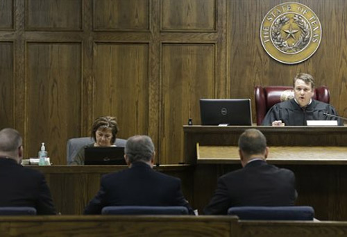 Judge Jason Cashon, back right, speaks to Eddie Ray Routh, left, and his lawyers Tim Moore, front right, and J. Warren St. John during a pretrial proceeding, Tuesday, Feb. 10, 2015, in Stephenville, Texas. The former Marine is accused of killing Navy SEAL sniper Chris Kyle and Kyle's friend Chad Littlefield at a gun range on Feb. 2, 2013. (AP Photo/LM Otero, Pool)