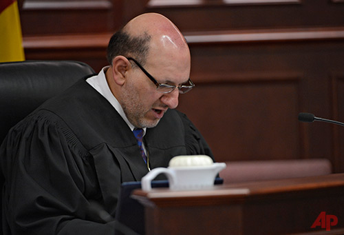In this Tuesday, June 4, 2013, file photo, Judge Carlos A. Samour Jr. reads an advisement during a hearing for Aurora theater shooting suspect James Holmes in Centennial, Colo. Samour hopes to have a jury seated by late April 2015. Until then, attorneys from both sides are spending long days grilling jury prospects about their views on the death penalty, mental illness and their own personal problems. (AP Photo/The Denver Post, Andy Cross, Pool)