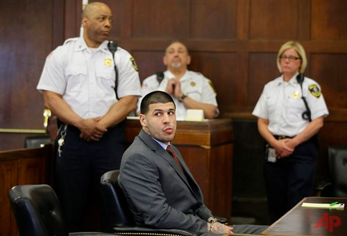 Former New England Patriots NFL football player Aaron Hernandez sits at the defendant's table while his attorneys participate in a sidebar discussion during his arraignment at Suffolk Superior Court, Thursday, May 21, 2015, in Boston, on a charge of trying to silence a witness in a double murder case against him by shooting the man in the face. (AP Photo/Stephan Savoia, Pool)