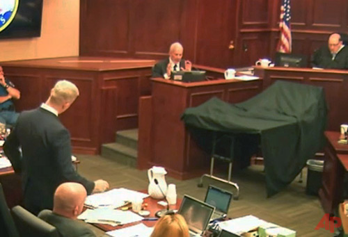District Attorney George Brauchcer, left, questions state-appointed psychiatrist Dr. Jeffrey Metzner, center, as Judge Carlos Samour, Jr., looks on at right during trial testimony in Centennial, Colo., Monday, June 8, 2015. Metzner testified that Colorado theater shooter James Holmes was mentally ill at the time of a deadly attack that killed 12 people and wounded 70 others during the midnight premiere of a Batman film. (Colorado Judicial Department via AP, Pool)