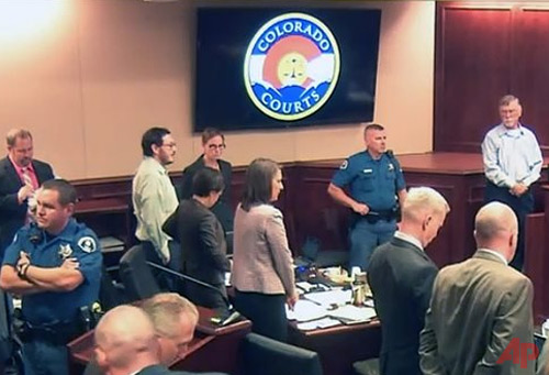 In this image made from Colorado Judicial Department video, Robert Holmes, top right, the father of James Holmes, background second from left, and others stand as the jury enters the courtroom during the sentencing phase of the Colorado theater shooting trial in Centennial, Colo., Tuesday, July 28, 2015. The father of the Colorado theater shooter said he didn't know his son suffered from mental illness until he killed 12 people at a Batman movie. (Colorado Judicial Department via AP, Pool)