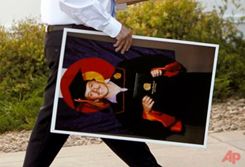 In this July 27, 2012, file photo, a funeral director carries a photo of Colorado movie theater shooting victim AJ Boik for display at his funeral mass at Queen of Peace Catholic Church in Aurora, Colo. Boik was 18 and had just graduated from Gateway High School in Aurora. He was to start classes at the Rocky Mountain College of Art and Design in the fall of 2012. (AP Photo/Ed Andrieski, File)