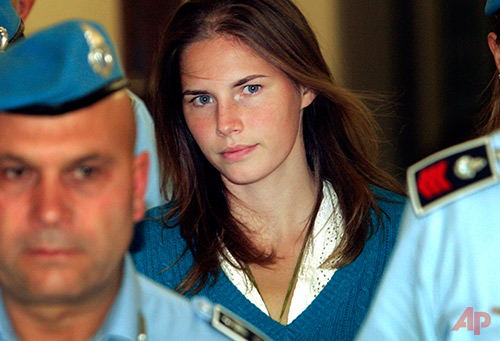 In this Sept. 26, 2008 file photo, Amanda Knox, center, is escorted by Italian penitentiary police officers to Perugia's court. Italy's top criminal court has scathingly faulted prosecutors for presenting a flawed and hastily constructed case against Amanda Knox and her former Italian boyfriend, saying Monday, Sept. 7, 2015 it threw out their convictions for the 2007 murder of her British roommate in part because there was no proof they were in the bedroom where the woman was fatally stabbed. (AP Photo/Pier Paolo Cito, File)