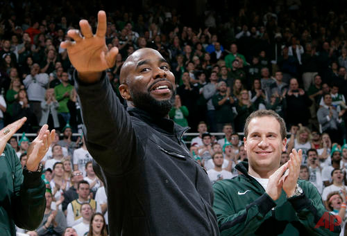 In this Dec. 21, 2015 file photo, former Michigan State player Mateen Cleaves, left, waves as he is introduced with Michigan State's 2000 national championship team during halftime of Michigan State-Florida NCAA college basketball game in East Lansing, Mich. Cleaves faces charges after a woman says she was held against her will in a motel room and sexually assaulted. Wayne County Prosecutor Kym Worthy says the 39-year-old Cleaves was charged Tuesday March 15, 2016, with criminal sexual conduct, assault with intent to commit criminal sexual penetration and unlawful imprisonment. (AP Photo/Al Goldis, File)