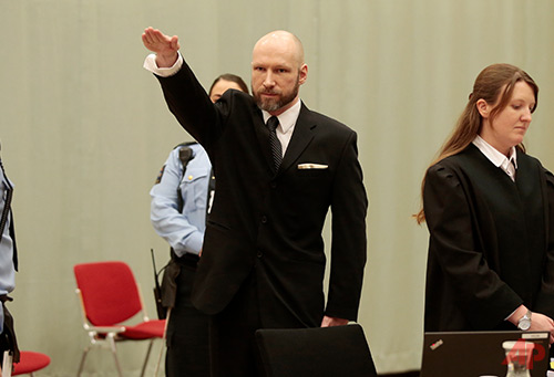 Anders Behring Breivik raises his right hand at the start of his appeal case in Borgarting Court of Appeal at Telemark prison in Skien, Norway, Tuesday, Jan. 10, 2017. Norwegian mass murderer Anders Behring Breivik walked quietly into a courtroom at a high security prison Tuesday, making a neo-Nazi salute, as judges began reviewing a government appeal against a ruling that his solitary confinement was inhumane and violated human rights. (Lise Aaserud/NTB Scanpix via AP)