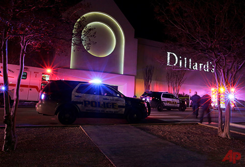 San Antonio police stand guard at an exit to the Rolling Oaks Mall after a deadly shooting Sunday, Jan. 22, 2017, in San Antonio. Authorities say several were injured after a robbery at the shopping mall. (AP Photo/Eric Gay)