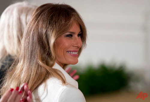 This is a Wednesday, March 29, 2017, file photo of U.S. first lady Melania Trump smiles as she is recognized by President Donald Trump as he speaks at a women's empowerment panel, in the East Room of the White House in Washington. Melania Trump on Wednesday April 12, 2017, accepted an apology and damages from the publisher of the Daily Mail newspaper for reporting rumors about her time as a model. (AP Photo/Andrew Harnik, File)