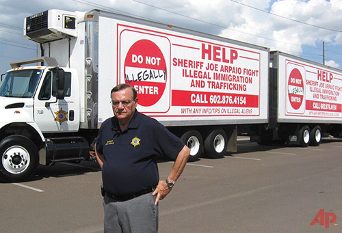In this Sept. 16, 2007, file photo, Maricopa County Sheriff Joe Arpaio shows off vehicles advertising a hotline to report undocumented immigrants in Phoenix, Ariz. Arpaio has been convicted of a criminal charge Monday, July 31, 2017, for disobeying a court order to stop traffic patrols that targeted immigrants in a conviction that marks a final rebuke for the former sheriff and politician who once drew strong popularity from such crackdowns but was booted from office amid voter frustrations over his deepening legal troubles. (Larry Fehr-Snyder/Arizona Republic via AP, file)