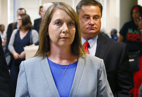 In this May 17, 2017, file photo, Betty Shelby leaves the courtroom with her husband, Dave Shelby, right, after the jury in her case began deliberations in Tulsa, Okla. Shelby, a former Tulsa police officer who resigned after being acquitted of manslaughter in the fatal shooting of an unarmed black man, is going to work for the sheriff's office in neighboring Rogers County. (AP Photo/Sue Ogrocki, File)