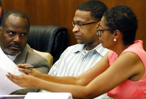 Defense attorneys Alton Peterson, left, and Darla Palmer, right, consult with their client, Quinton Tellis, 29, who is charged with burning 19-year-old Jessica Chambers, to death almost three years ago, during closing arguments in his capital murder trial in a courtroom in Batesville, Miss., Sunday, Oct. 15, 2017. (AP Photo/Rogelio V. Solis, Pool)